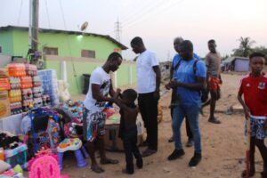 A staff of Enough Grace Foundation dressing a child whiles VMF members looks on